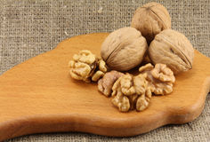 Walnuts on a wooden board (cutting board). On a background of natural burlap Royalty Free Stock Images