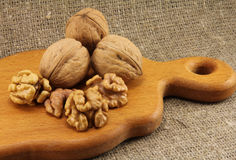 Walnuts on a wooden board (cutting board). On a background of natural burlap Royalty Free Stock Image