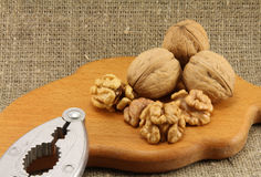 Walnuts on a wooden board (cutting board) with a nutcracker. On a background of natural burlap Stock Photo