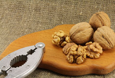 Walnuts on a wooden board (cutting board) with a nutcracker. On a background of natural burlap Royalty Free Stock Photography