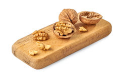 Walnuts on wooden boeard ower white. Walnuts on wooden board. Close-up isoated on white background stock photo