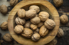 Walnuts in a wooden bowl on a rustic wooden background, top view, close up. Walnuts in a wooden bowl on rustic wooden background, top view, close up royalty free stock images