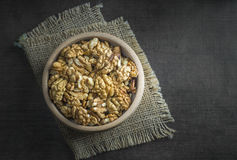 Walnuts in the wooden bowl on table. From above Stock Photo