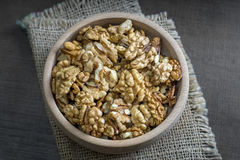 Walnuts in the wooden bowl on table Stock Photography