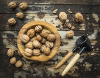 Walnuts in a wooden bowl on a wooden rustic background with tongs for cracking nuts,top view. Walnuts in a wooden bowl on wooden rustic background with tongs for royalty free stock image