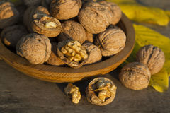 Walnuts in a wooden plate on old table. Walnuts in a wooden plate on rustic old table Royalty Free Stock Photography