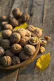 Walnuts in a wooden plate on  old table. Walnuts in a wooden plate on rustic old table Stock Images