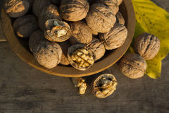 Walnuts in a wooden plate on rustic  table. Walnuts in a wooden plate on rustic old table Royalty Free Stock Photo