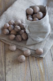 Walnuts on a wooden table. Walnuts in a cotton bag on a wooden table covered with burlap Stock Photos
