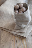 Walnuts on a wooden table. Walnuts in a cotton bag on a wooden table covered with burlap Royalty Free Stock Images