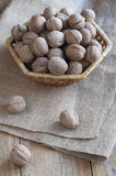 Walnuts on a wooden table. Walnuts in a wicker basket on a wooden table covered with burlap Stock Photo