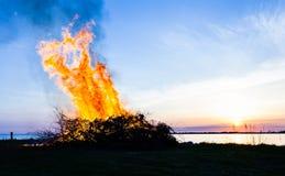 Walpurgis night fire by the sea in Klintehamn in Gotland. Silhouette of a Bonfire in sunset by the sea in Klintehamn Sweden Royalty Free Stock Photography