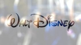 Walt Disney Pictures logo on a glass against blurred crowd on the steet. Editorial 3D rendering. Walt Disney Pictures logo on a glass against blurred crowd on stock video footage