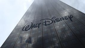 Walt Disney Pictures logo on a skyscraper facade reflecting clouds, time lapse. Editorial 3D rendering. Walt Disney Pictures logo on a skyscraper facade stock footage
