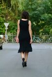 Waltking woman. A  woman with a black dress takes a walk in the city Stock Photography