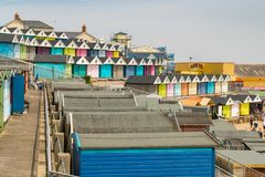 Walton-on-the-Naze, Essex, England, UK. May 29, 2017: Rows of beach huts at the Southcliff Promenade, with some people and the Walton Pier in the background Stock Photography