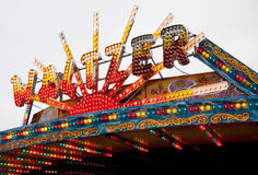 Waltzer fairground lights sign. The Waltzer is a traditional funfair ride, its colourful sign is shown here with multi-colored flashing lights Stock Image
