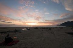 Waman watching sunset. Woman sitting near small fire watching the sunset Royalty Free Stock Photography