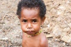 Wamena, Indonesien - 9. Januar 2010: Portret des Dani-Stammkindes Kleines Mädchen, welches die Kamera betrachtet Baliem-Tal in In stockbild