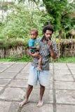 Wamena Indonezja, Stycze?, - 9, 2010: M??czyzna z dzieciakiem Dani plemi? w zwyk?ej odzie?owej pozycji w Dugum Da? wiosce zdjęcie royalty free