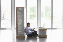 Wan With Cellphone And Laptop Between Packages At Empty Office Royalty Free Stock Photo