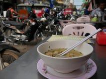 Wan Tan soppa i den vita bunken med mopeder och gataplats i bakgrund Arkivfoto
