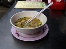 Wan Tan Soup en el cuenco blanco con la consumición de los palillos Foto de archivo libre de regalías