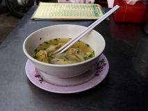 Wan Tan Soup in white bowl with eating sticks. Wan Tan soup in white bowl and eating sticks Royalty Free Stock Photo