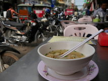 Wan Tan soup in white bowl with motorbikes and street scene in background. Wan Tan soup in white bowl with a restaurant menu and motorbikes and a street scene in Stock Photo