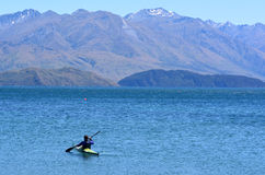 Wanaka - New Zealand. Man rows a kayak in Wanaka lake in the Otago region of the South Island of New Zealand Royalty Free Stock Photography