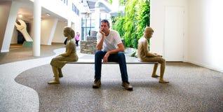 Wanaka, Nieuw Zeeland - Febr 5, 2015: de jonge mens zit op de bank in de Sculpt Illusiegalerij royalty-vrije stock afbeeldingen