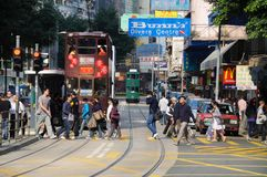 WANCHAI, HONG KONG - MARCH 26, 2012 - Pedestrians cross Johnston Road in front of a Hong Kong tram in the Wan Chai district of Hon Royalty Free Stock Images