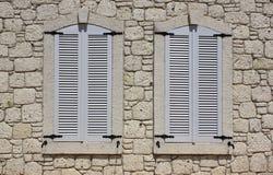 Wand der Kalksteinmaurerarbeit mit Fenstern stockfoto