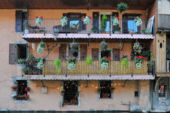 Wand des alten Hauses mit Fensterläden geschlossenen Fenstern und Balkonen entkernte bunte Blumen in den Blumentöpfen Stockfotografie