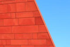Wand des roten Backsteins über blauem Himmel Stockfotografie
