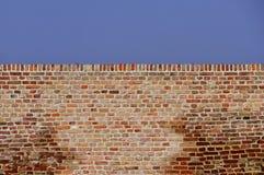 Wand des roten Backsteins gegen blauen Himmel Lizenzfreies Stockbild