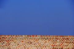 Wand des roten Backsteins gegen blauen Himmel Lizenzfreie Stockfotografie