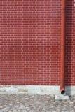 Wand des roten Backsteins mit Abflussrohr Stockfoto
