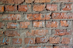 Wand des roten Backsteins mit Aufschriften in der Kreide Stockfoto