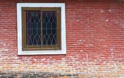 Wand des roten Backsteins mit einem Fenster Stockfoto
