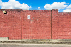 Wand des roten Backsteins mit einem Warnzeichen Stockbilder