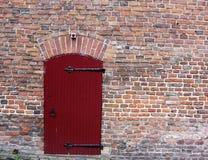 Wand des roten Backsteins mit einer Tür Stockfotografie