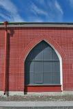 Wand des roten Backsteins mit Fenster und Abflussrohr Lizenzfreies Stockbild