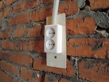 Wand des roten Backsteins mit weißem elektrischem Steckersockel in der Garage stockfotografie