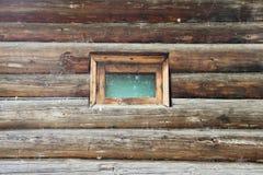 Wand eines Blockhauses mit einem kleinen Fenster Lizenzfreie Stockbilder