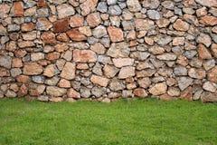 Wand hergestellt mit natürlichen Steinen und Gras in der Frontseite Stockfotos