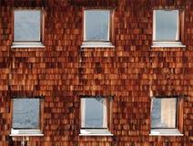 Wand hergestellt von den hölzernen Fliesen mit sechs Fenstern, die Schnee reflektieren lizenzfreies stockbild