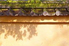 Wand mit altem mit Ziegeln gedecktem Dach Stockfotos