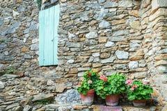 Wand mit einem Azurblau schließen mit in Pelargonien der Front drei herein Fensterläden stockfotos