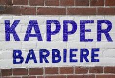 Wand mit Friseursalontext auf niederländisches und italienisch stockfotos
